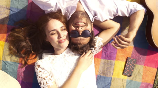 happy lovely young couple lying on colorful blanket in the park looking at the sky pointing clouds romantic with guitar sunglasses beautiful attractive girl top view rotating camera slow motion - picnic video stock e b–roll