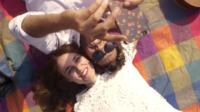 幸せな素敵な若いカップル取って selfies スマート フォンをギター サングラスとロマンチックな公園でカラフルな毛布の上に横たわる美しい魅力的な女の子トップ ビュー カメラ スローモーションを回転 ビデオ