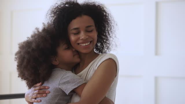 Happy loving black mother hugging cute little child daughter cuddling