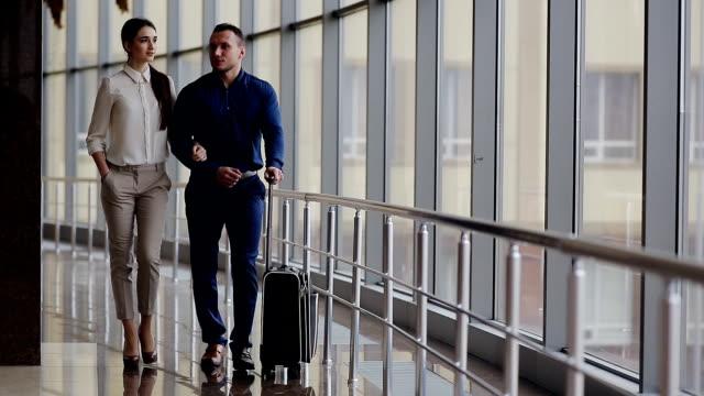 幸せなカップルのお気に入りのカジュアルウェアとの散歩、お荷物を空港ターミナルます。 ビデオ