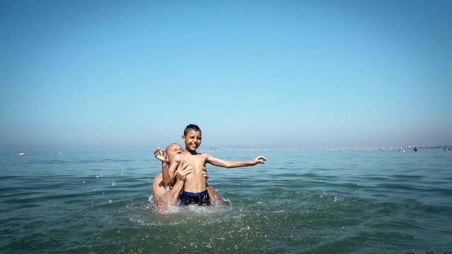vídeos de stock, filmes e b-roll de família loving feliz do pai e do filho que jogam, que saltam e que têm o divertimento na água de mar na praia-verão, curso, férias e conceito da família em slow motion - férias na praia