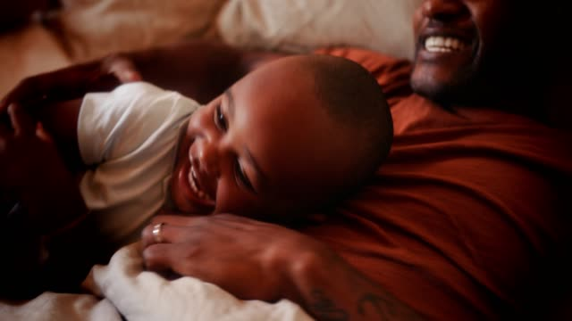 Happy loving father playing with little son in bed video
