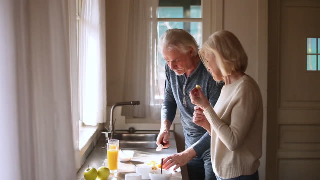 Happy loving senior mature couple having fun preparing healthy breakfast Happy loving senior mature couple having fun preparing healthy breakfast food in kitchen, playful old aged smiling family talking laughing cooking cutting apple feeding each other together at home mature adult stock videos & royalty-free footage