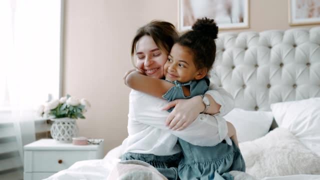 glad kärleksfull ung mamma europeisk i vit skjorta med sin charmiga lilla afrikanska dotter på stor ljus säng i sovrummet på morgonen. omtänksam mamma hjälpte knäppa upp baby blå klänning. kramas och kysser henne - cosy pillows mother child bildbanksvideor och videomaterial från bakom kulisserna