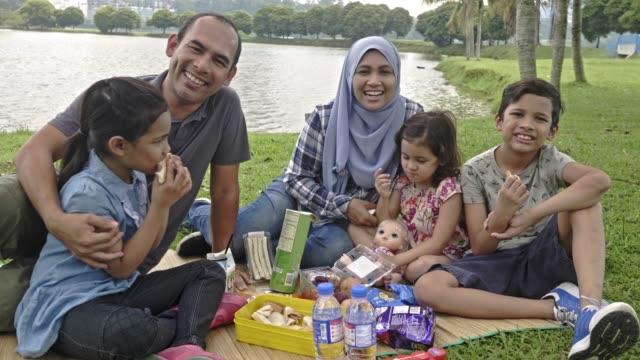 stockvideo's en b-roll-footage met gelukkig maleis familie genieten in het park - maleisië