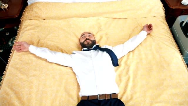 happy male businessman jumping on bed at hotel room having business trip slow motion - leżeć filmów i materiałów b-roll