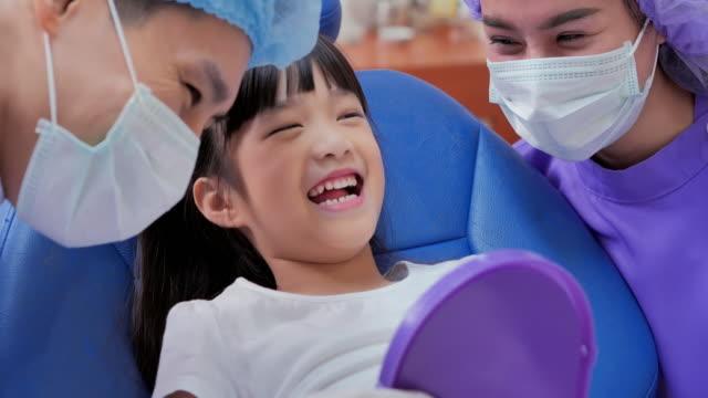vídeos y material grabado en eventos de stock de feliz dentista masculino con espejo de verificación de los dientes de niña paciente en la oficina de la clínica dental. linda niña sentada en la silla dental y teniendo tratamiento dental. medicina, estomatología y concepto de atención médica. chequ - ortodoncista