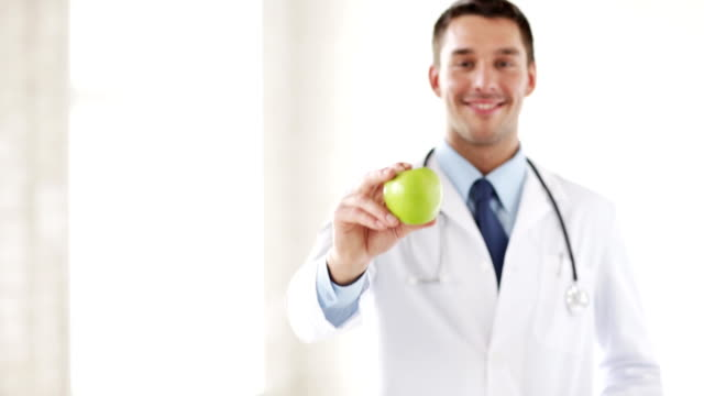 happy male doctor with green apple medicine, healthcare and diet concept  -  happy male doctor with green apple nutritionist stock videos & royalty-free footage