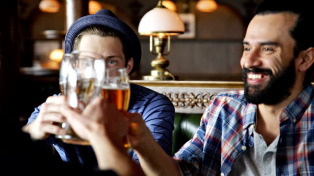 happy male friends drinking beer at bar or pub - england stock videos & royalty-free footage