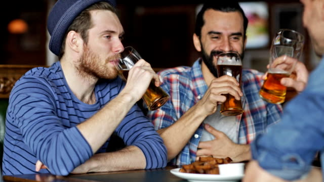 happy male friends drinking beer, eating snacks and clinking glasses at bar or pub video