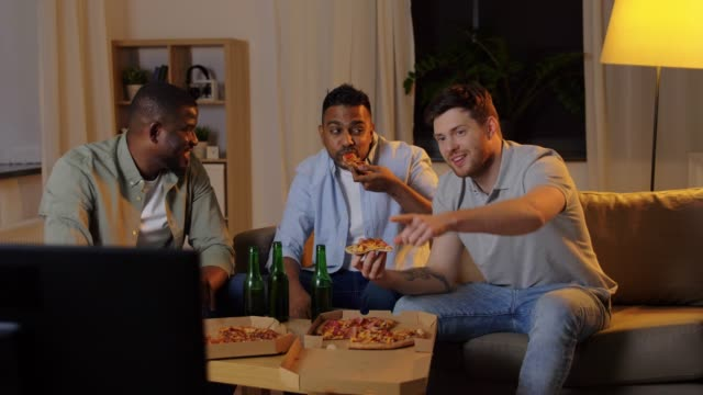 happy male friends with beer eating pizza at home