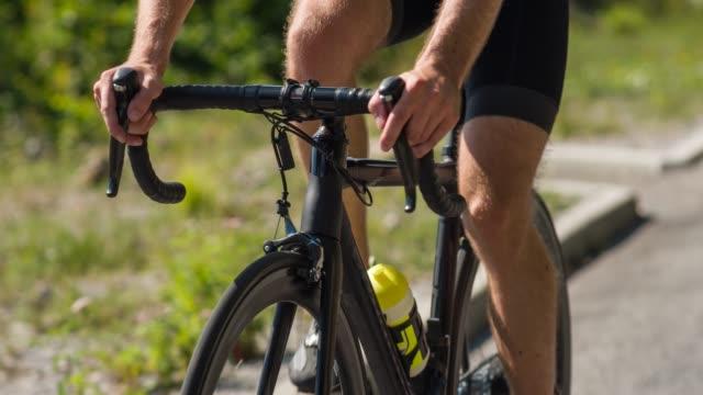 happy male road cyclist pedaling uphill empty mountain road - ciclismo su strada video stock e b–roll
