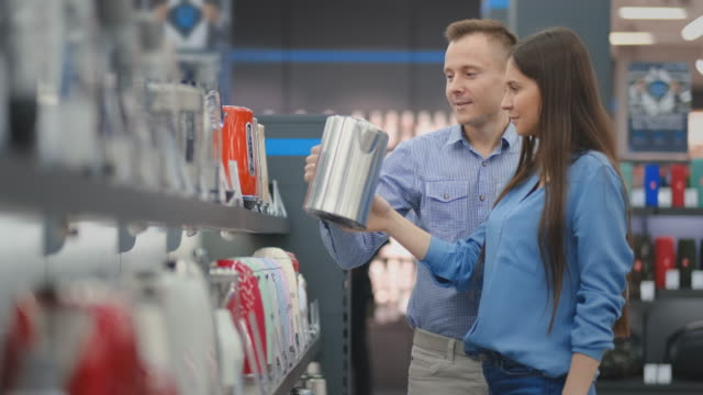 Happy man and woman choose an electric tea tree for their home in a hardware and electronics store Happy man and woman choose an electric tea tree for their home in a hardware and electronics store. department store stock videos & royalty-free footage