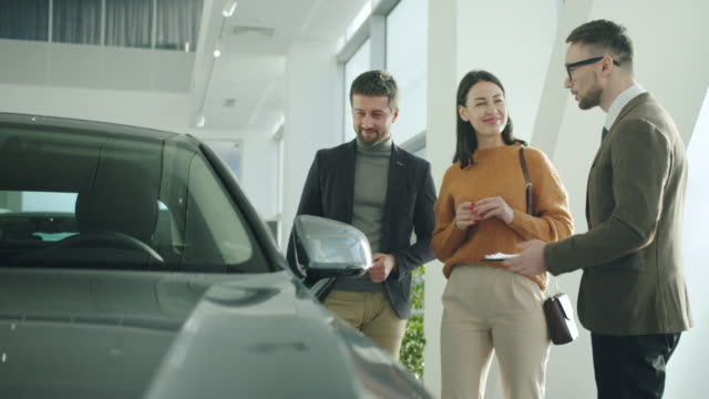 Happy man and woman talking to car dealer in dealership discussing automobiles video