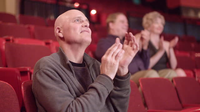 Happy man applauding in slow motion at end of a movie video