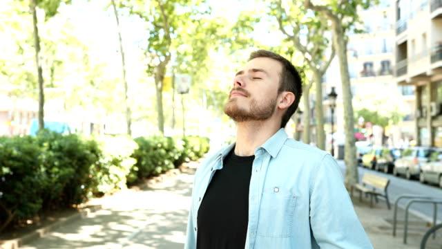 glücklicher mann atmet frische luft in einer stadtstraße - atemübung stock-videos und b-roll-filmmaterial