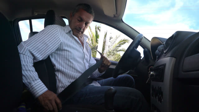 Happy man buckling his seat belt and starting the car