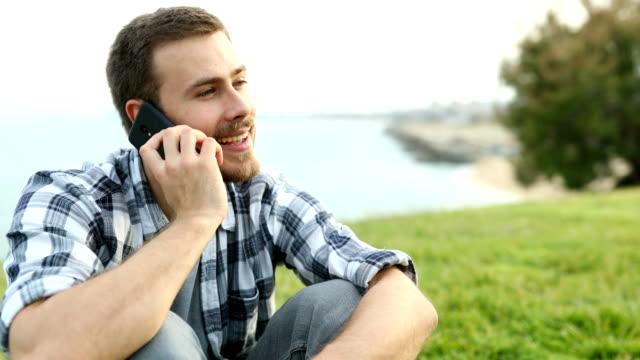 happy man calling on phone outdoors - ear talking video stock e b–roll