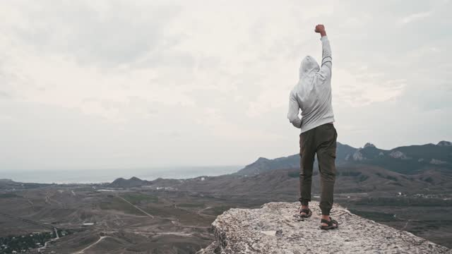 Happy man climbing on top of cliff and raises hand his fist up.