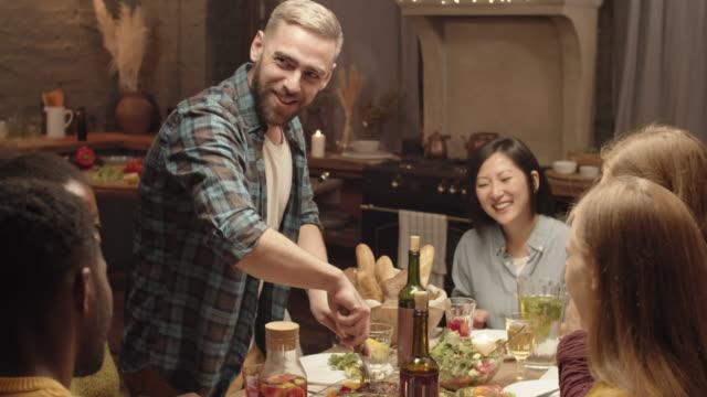 저녁 식사 파티 중 스테이크를 절단 해피 맨 - 와인병 스톡 비디오 및 b-롤 화면