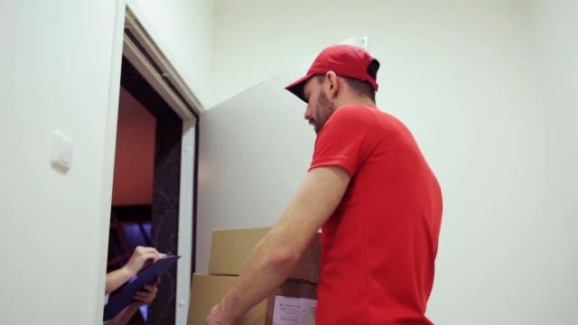 快樂的人送包裹箱子到顧客家 - postal worker 個影片檔及 b 捲影像