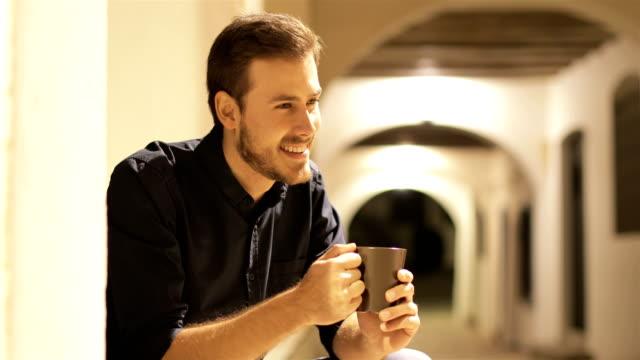 vidéos et rushes de café potable heureux d'homme dans la rue dans la nuit - man drinking terrace