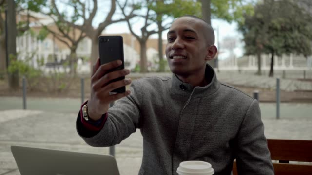 vídeos de stock e filmes b-roll de happy man drinking coffee to go and having video chat outdoor - esplanada portugal