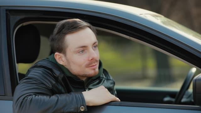 vidéos et rushes de chauffeur heureux d'homme agitant à quelqu'un - homme faire coucou voiture