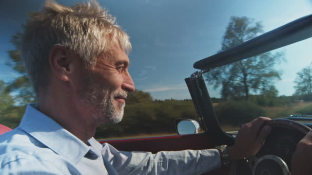 happy man driving vintage car on sunny day - capelli grigi video stock e b–roll