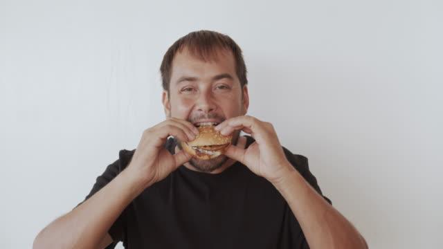 Gelukkige man eten smakelijke Fast food hamburger video