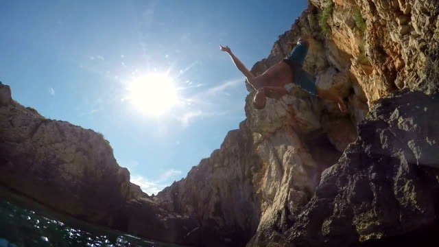 SLOW MOTION UNDERWATER: Happy man flip jumping into water on fun summer vacation video