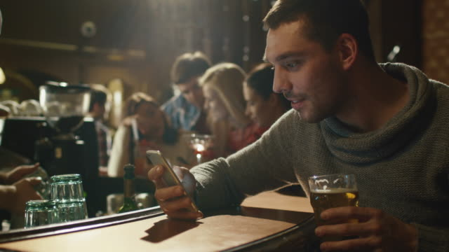 Happy man holds a glass of beer while using a smartphone in a bar. video