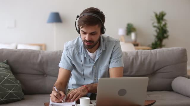 Video Happy man in headset speaking by webcam looking at laptop
