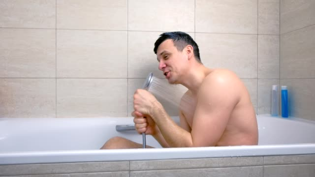Happy man is singing while he is washing in bathtub. video