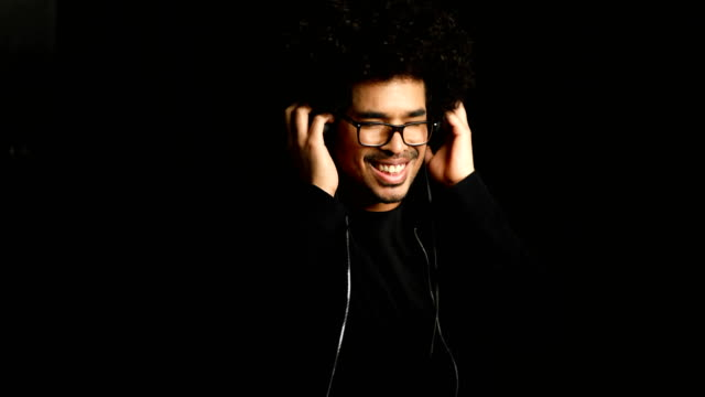 Happy man listening music through headphones Lockdown shot of smiling man listening music through headphones. Happy male is enjoying against black background. He is wearing casuals. eyes closed stock videos & royalty-free footage