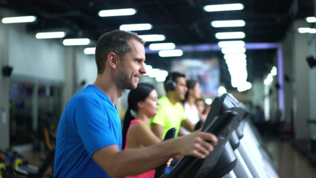 Happy man on the elliptical machine at the gym Happy man on the elliptical machine at the gym and a group of people behind also exercising health club stock videos & royalty-free footage