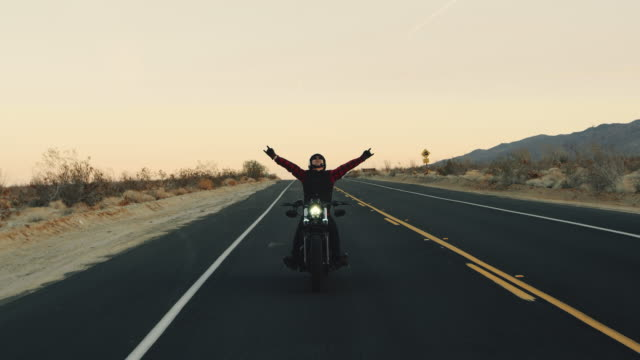 Happy man riding motorcycle at sunset celebrating with arms raised in air 4k slow motion shot of happy adventurous man riding black motorcycle down desert highway at sunset motorcycle stock videos & royalty-free footage