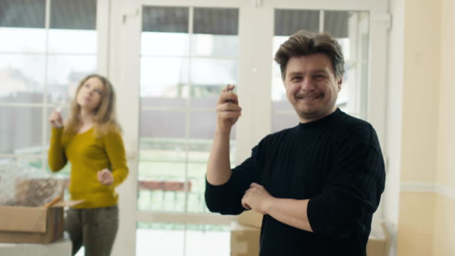 Glücklicher Mann zeigt Schlüssel von einem neuen Haus – Video