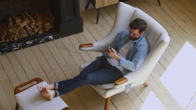 Happy man sit on comfortable chair in house using phone Happy young man sit on comfortable chair in modern country house room with fireplace relax hold smartphone using phone apps play mobile games lounge at cozy home on wooden floor, top view from above lounge chair stock videos & royalty-free footage