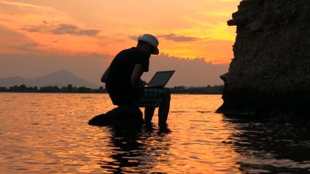 lycklig man sitter på stenen och arbetar vid datorn med havsutsikt, statisk ram. manlig silhuett på solnedgång seascape bakgrund. resor bloggare som arbetar på havet. freelancer koncept. - map oceans bildbanksvideor och videomaterial från bakom kulisserna