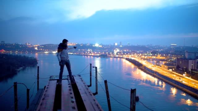 uomo felice in piedi in cima al ponte e indicando una splendida vista sulla città notturna - sezione superiore video stock e b–roll