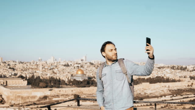 Happy man takes selfie in old town Jerusalem. Bearded local male smiles happy, taking photos. Perfect Israel panorama 4K video