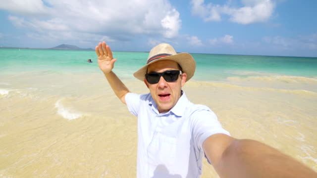 vídeos de stock e filmes b-roll de happy man taking a selfie on hawaiian beach in 4k slow motion - homem chapéu