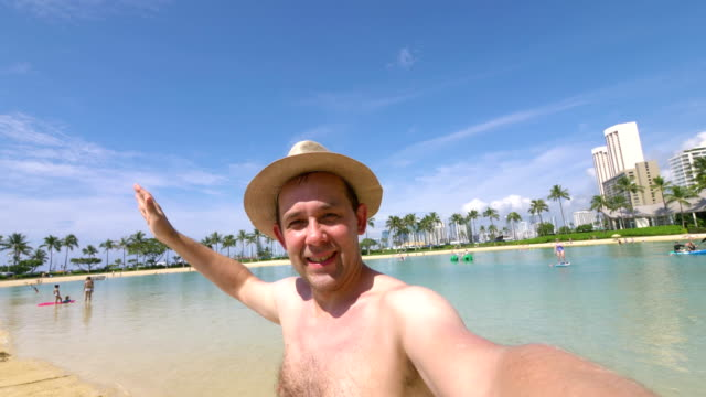 Happy man taking a selfie on Waikiki beach Hawaii in 4k slow motion Professional video of happy man taking a selfie on Waikiki beach Hawaii in 4k slow motion 60fps waikiki stock videos & royalty-free footage