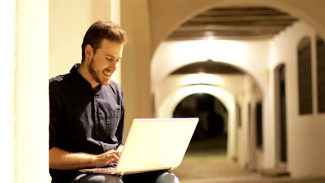 vídeos de stock, filmes e b-roll de homem feliz que usa um portátil na noite - mobile