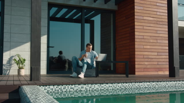vídeos de stock e filmes b-roll de happy man using laptop at luxury house. business man using technology at home - isolated house, exterior