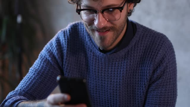 glücklicher mann mit telefon, um sms-nachrichten senden - online dating stock-videos und b-roll-filmmaterial