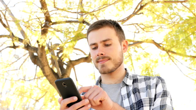 Happy man using smart phone in a park