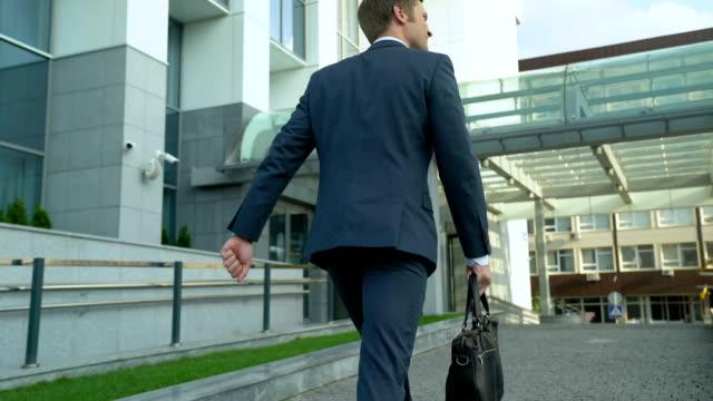szczęśliwy człowiek idący do biurowca, początek dnia pracy, pomyślna przyszłość - praca w sektorze handlowym filmów i materiałów b-roll