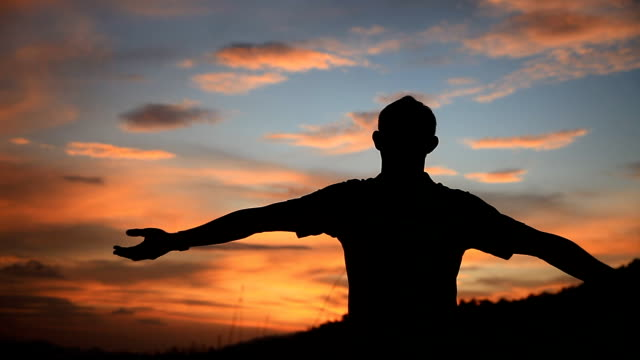 Happy man with hands raised spinning at sunset. - vídeo